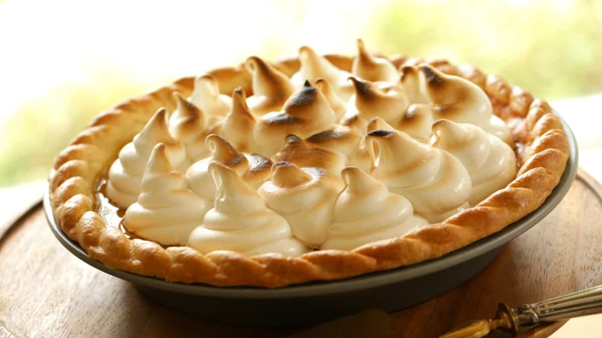 Pumpkin Pie with Marshmallow Topping served on a dark wood stand