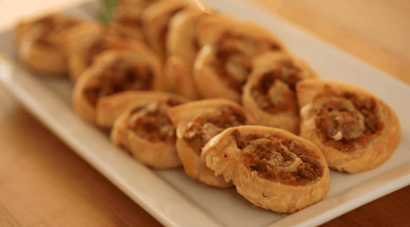 Freshly Baked Pinwheels with sausage and cheese on a rectangular platter