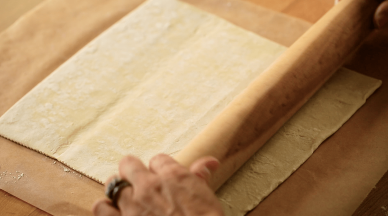 A person rolling puff pastry on a cutting board with a wooden rolling pin
