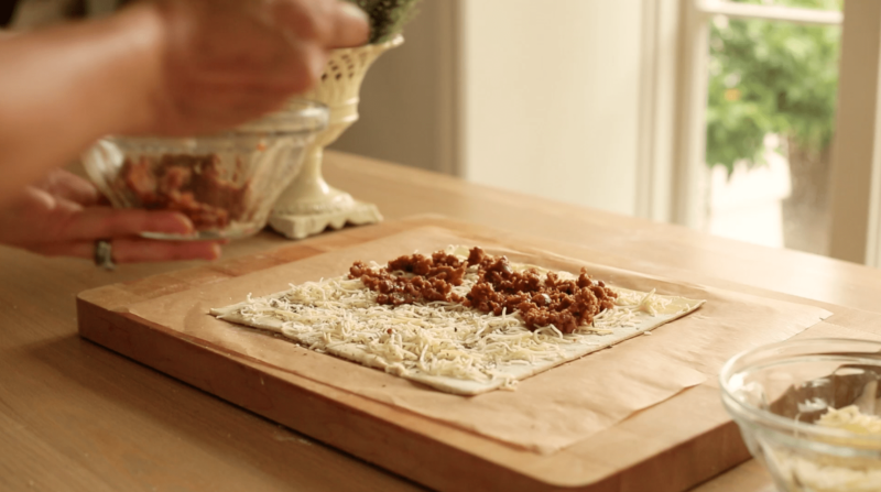 A sheet of puff pastry filled with grated cheese and cooked Italian Sausage on a table