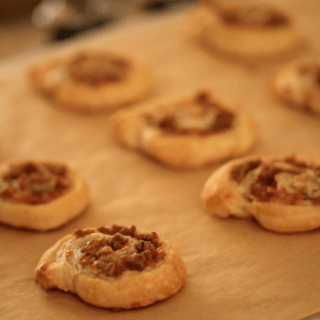 Freshly Baked Sausage and Cheese Pinwheels on a baking sheet lined with parchment paper