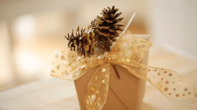 a fully packaged container of Peanut Brittle with gold ribbon and gold dipped Pine Cones