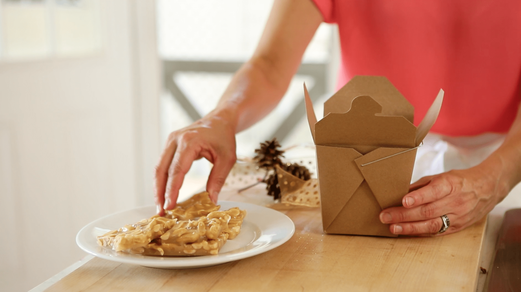 a person packaging up peanut brittle into a parchment Chinese Take out Container