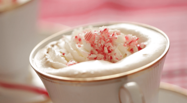 close up of whipped cream and crushed peppermint pieces on top of a how to make Peppermint Hot Chocolate recipe served in a white tea cup on top of a saucer