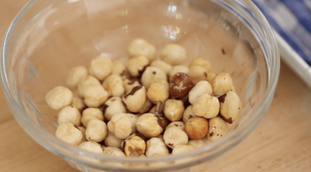 toasted hazelnuts without the skin in a small clear bowl for a Chocolate Hazelnut Biscotti recipe