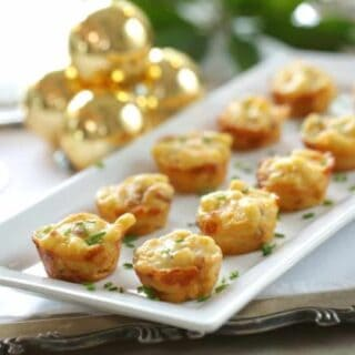 a white platter of mac and cheese bites with a fresh chive garnish