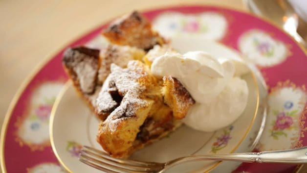 A square of Panettone Bread Pudding Recipe sliced on a place topped with whipped cream
