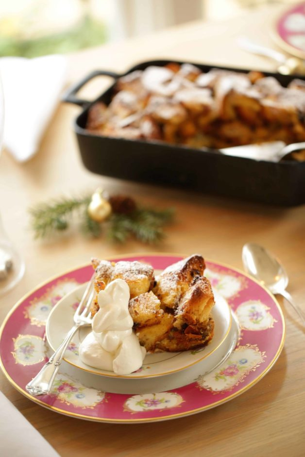 Panettone Bread Pudding Recipe. A serving on a plate with whipped cream and casserole in the background
