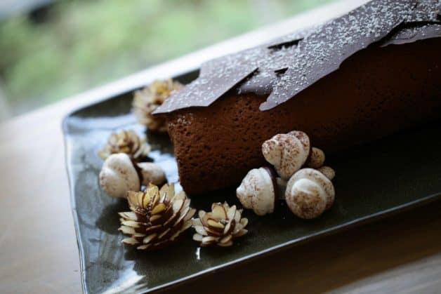 Buche de Noel cake on a green platter with candy pinecones and mushrooms