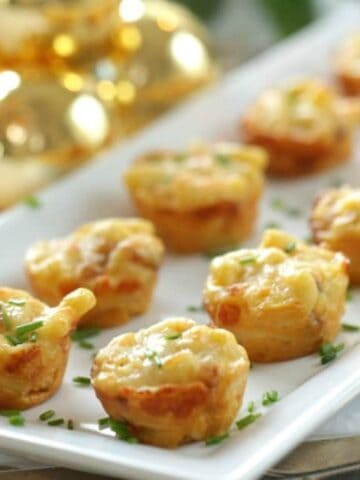 Bacon Mac and Cheese Bites baked and served on a white plate