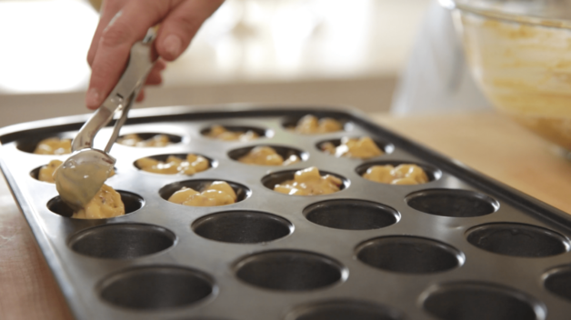 Bacon Mac & Cheese Bites being scooped into a mini muffin tin before baking