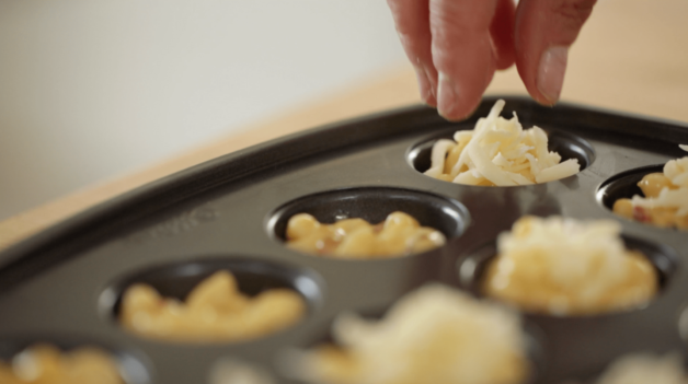 placing cheese on top of bacon mac and cheese bites before going into the oven