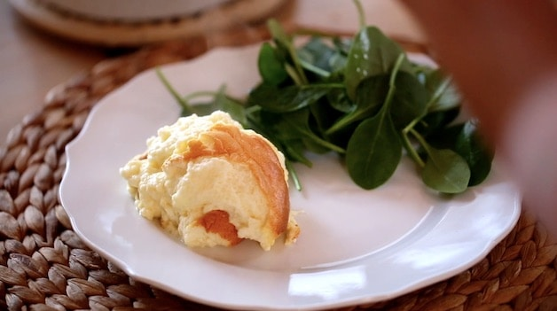 a scoop of cheese souffle on a plate with a salad