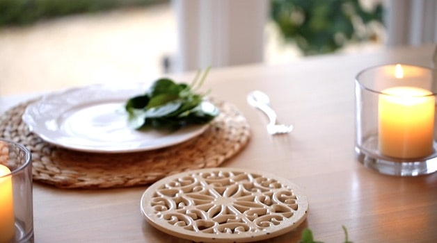 table set with plates of salad and a trivet
