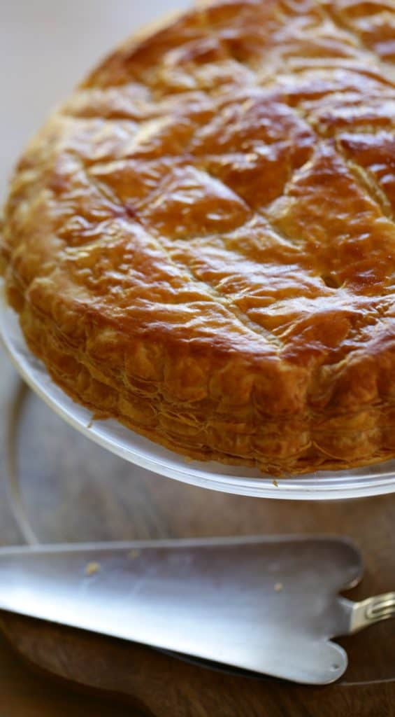 Galette Des Rois Recipe on a cake stand with server cake server