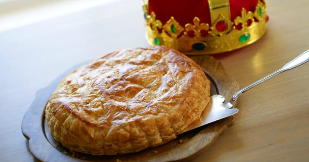 Galette Des Rois Recipe on a wooden plate with cake server and crown in the background