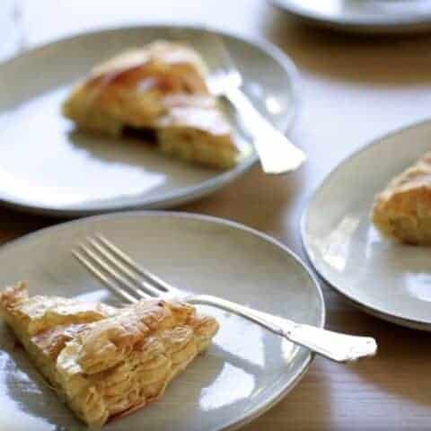 Slices of Galette des Rois cake on gray plates with forks