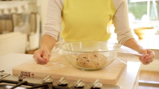 covering dough in a bowl with plastic wrap