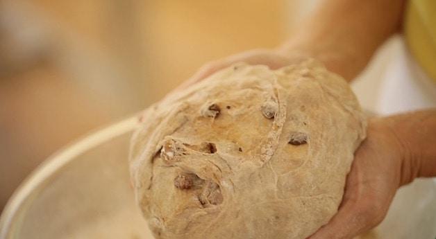 a ball of cinnamon raisin bread in hands