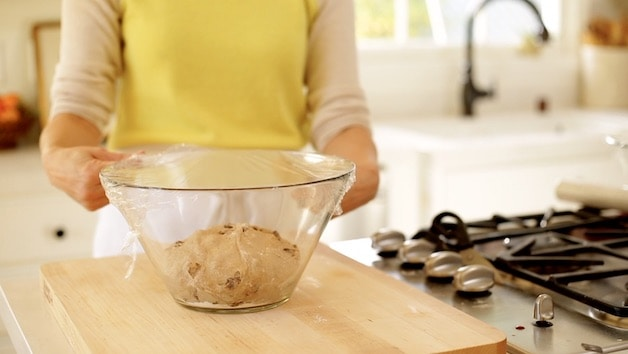 Dough ball in bowl covered with plastic wrap