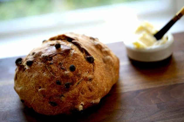 No-Knead Cinnamon Raisin Bread resting on a cutting board with a dish of butter