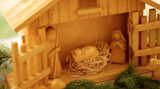 Nativity scene made from wood showing Jesus Mary and Joseph in the manger