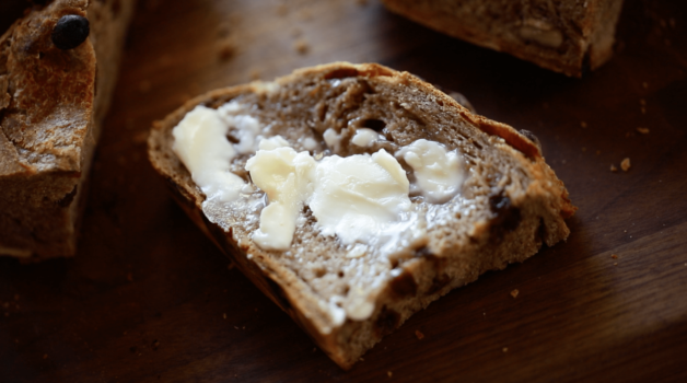 No Knead Cinnamon Raisin Bread sliced and slathered with butter