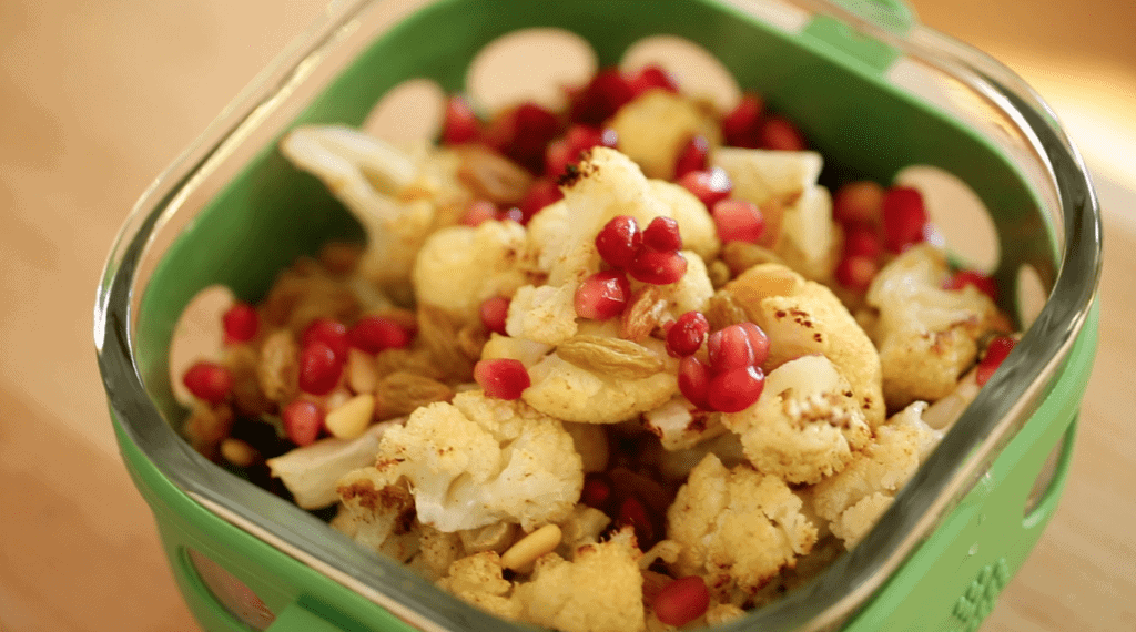 Roasted Cauliflower Salad with Pomegranate Seeds on top in a salad container