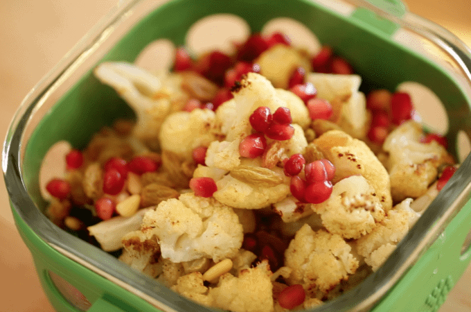 A close up of a plastic container filled with Cauliflower, pomegranate seeds, and golden raisins