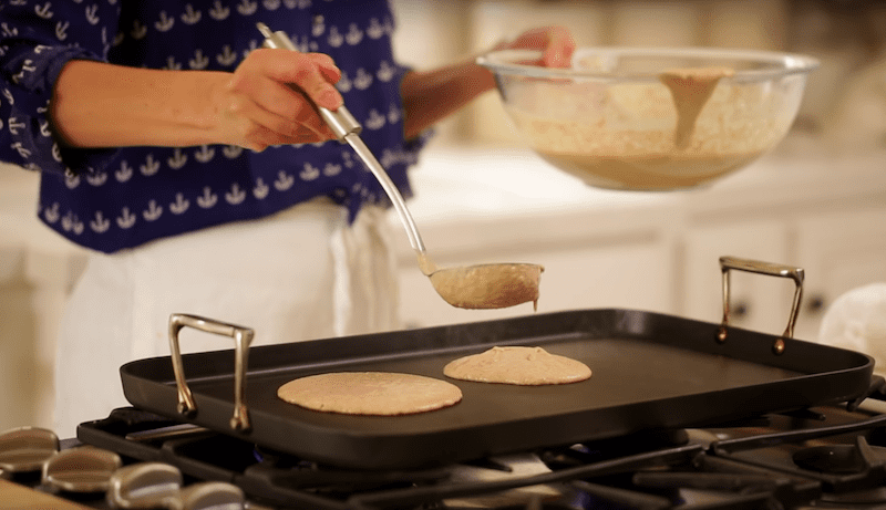 banana pancake recipe being ladled on to a hot griddle