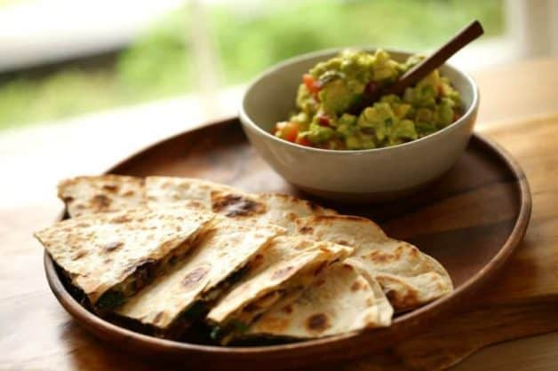 Veggie Quesadilla Recipe on a wooden platter with guacamole with Chunky Gaucomole served on a large wood bowl