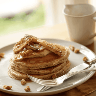 Banana Pancake Recipe served on a large plate with a knife and fork and a cup of coffee in the background