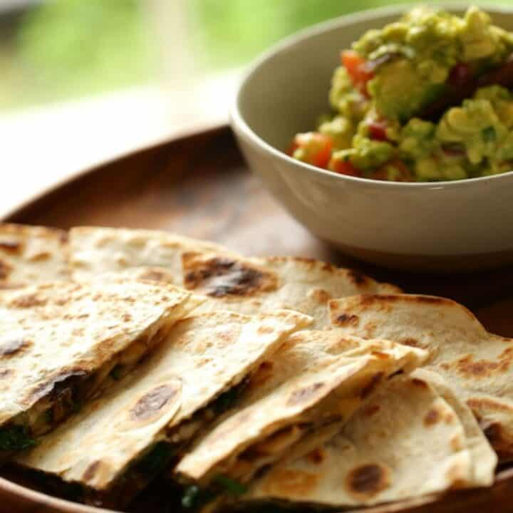 Veggie Quesadilla on a wooden serving platter with a bowl of chunky quacamole