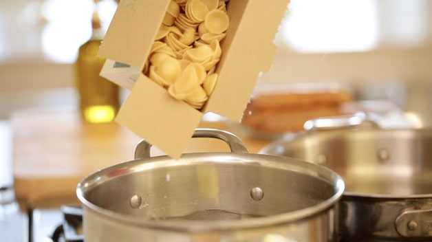 Box of pasta being poured into boiling water