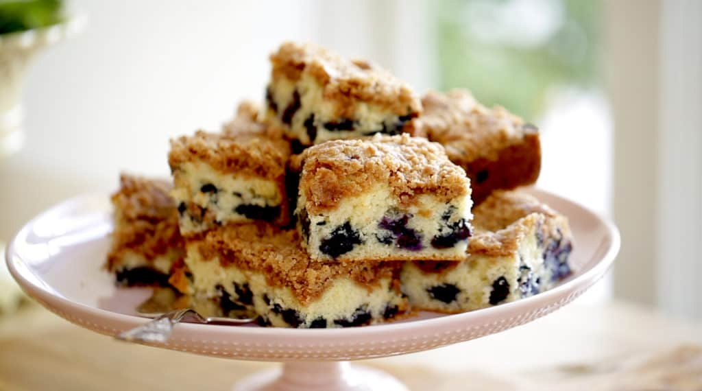 Blueberry Crumb Cake Recipe baked and cut served on a light pink cake stand