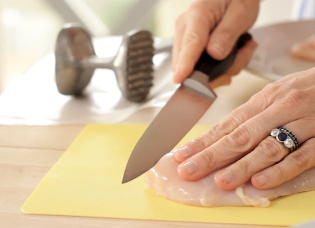 Slicing raw chicken breast in half on a yellow mat