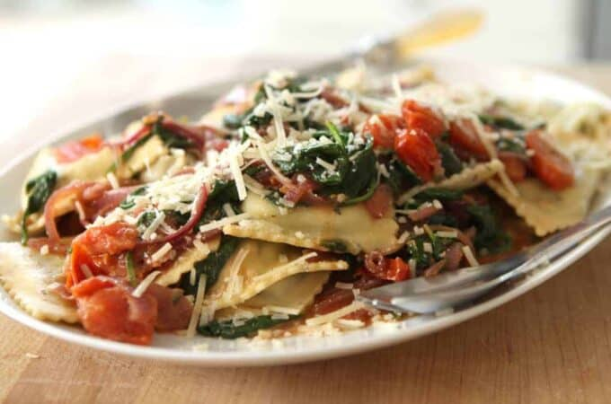 Spinach Ravioli with Spinach, Tomatoes, and Caramelized Onions on a white platter