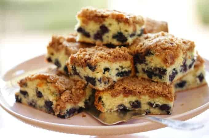 close up of Blueberry Crumb Cake Recipe baked and cut served on a light pink cake stand