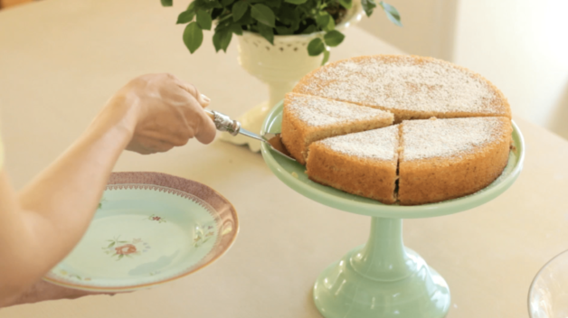 Orange Almond Cake on a green cake stand being served