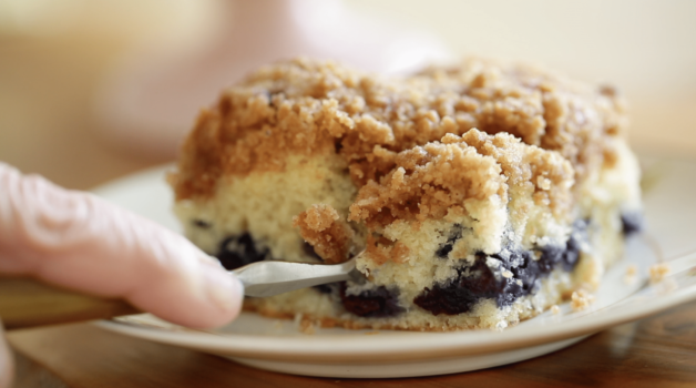 Blueberry Crumb Cake Recipe baked and served on a plate with a fork taking a bite