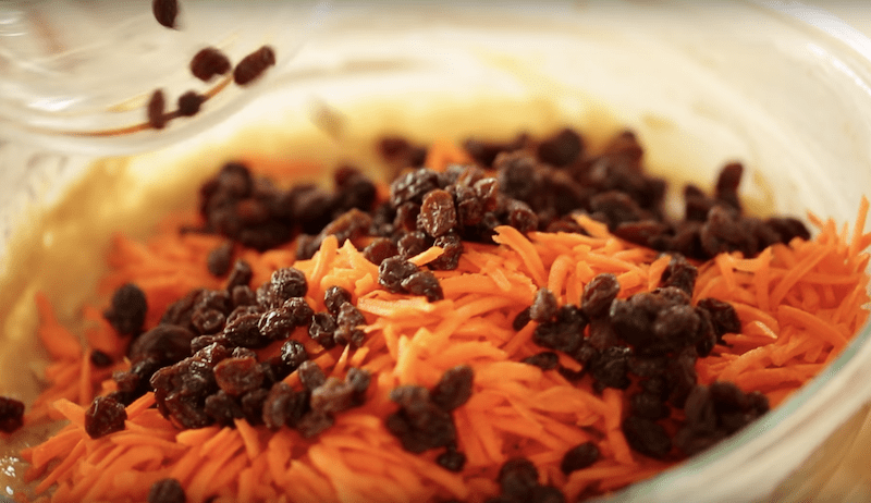 grated carrots and raisins added to the best carrot cake recipe in a large clear bowl