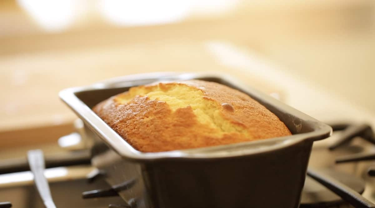 a pound cake freshly baked and cooling on a cooktop