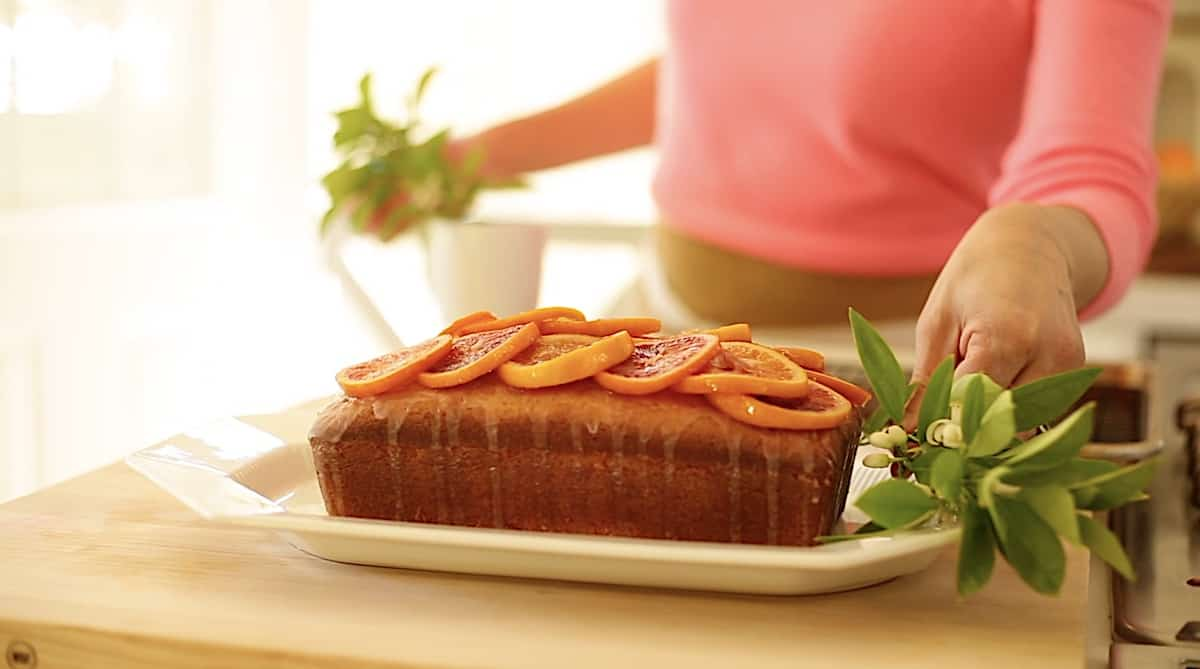 a person garnishing a pound cake with citrus blossoms
