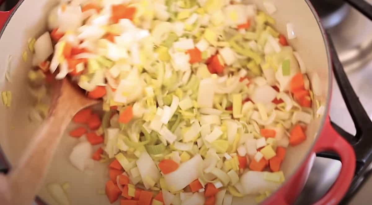 a mixture of leeks, carrots and white onion cooking in a Dutch oen