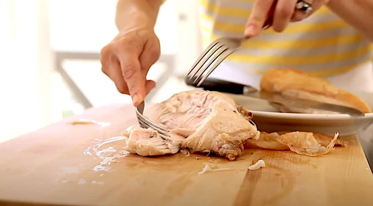 Shredding cooked chicken breast on a cutting board