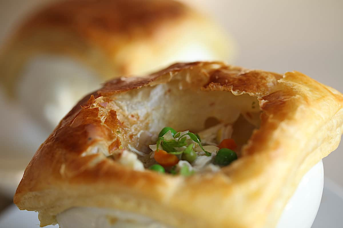 Chicken Pot Pie with puff pastry topping cut open to see filling inside
