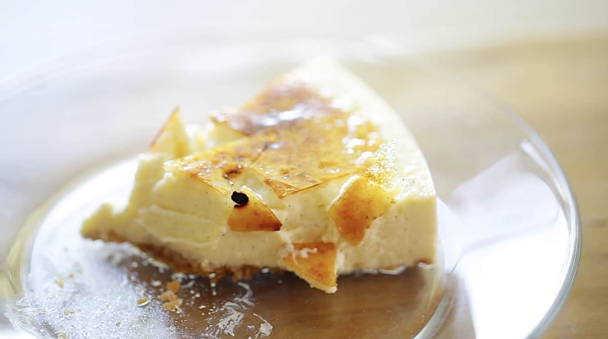 a slice of creme brulee cheesecake showing the crackling burnt sugar topping