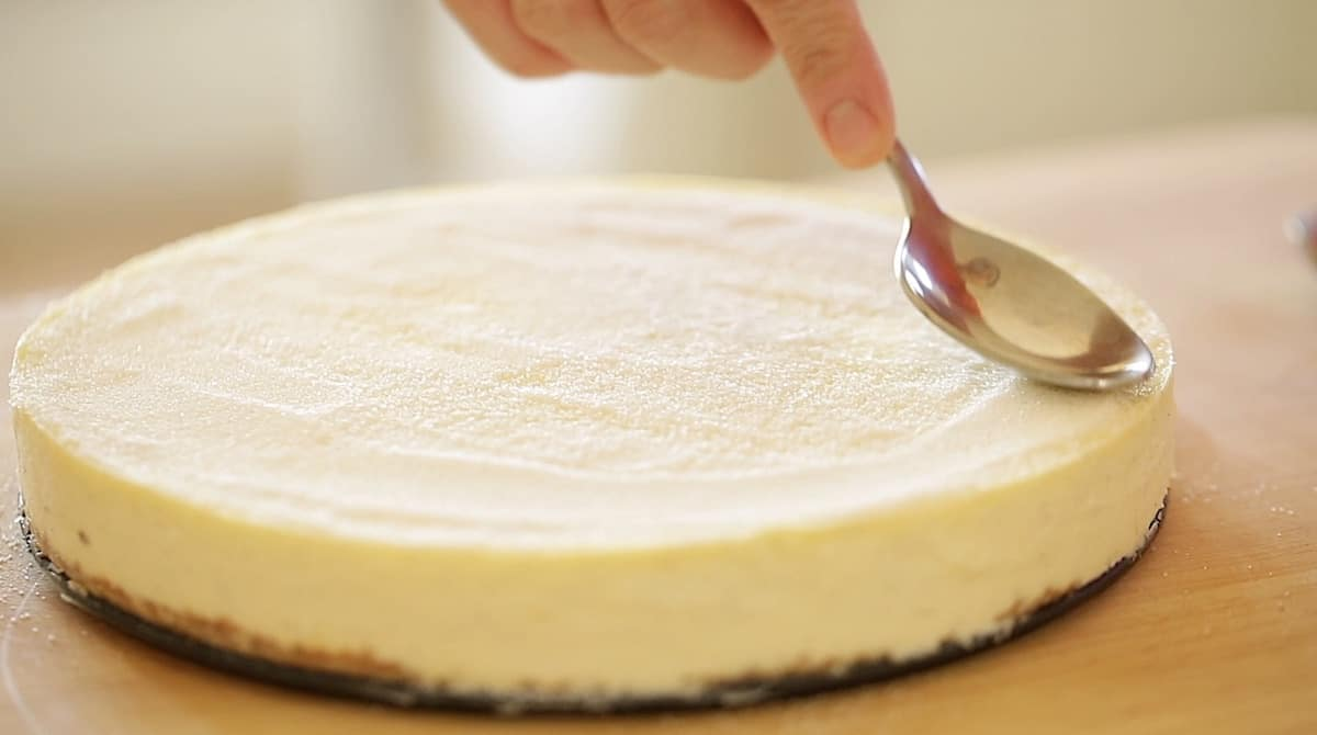 a person smoothing out a layer of sugar on top of cheesecake