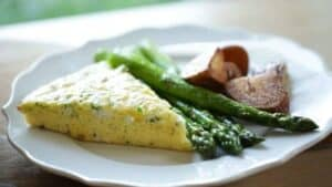 A slice of cheesy egg bake on a plate with roasted asparagus and roasted potatoes
