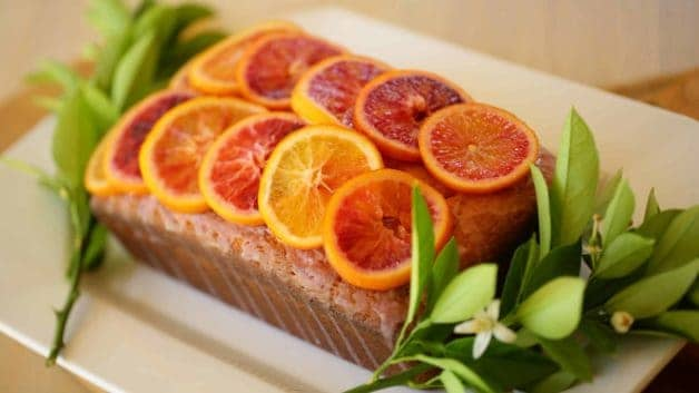 Blood Orange Pound Cake on white platter decorated with candied oranges and citrus leaves